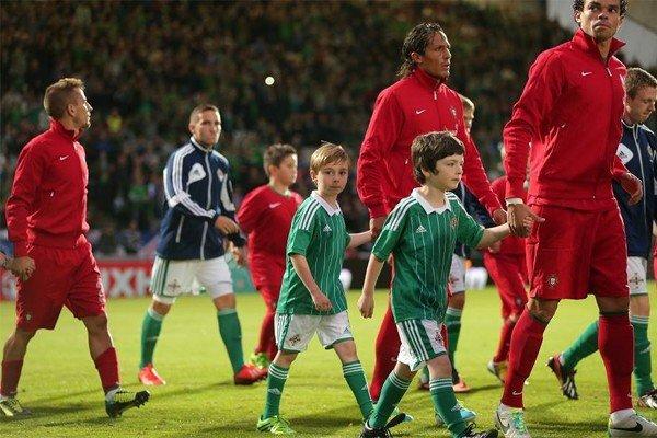 футболисты выходят на поле с детьми